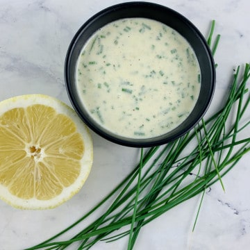 SOUR CREAM & CHIVE DRESSING IN A BLACK BOWL WITH CHIVES AND LEMON ON THE SIDE