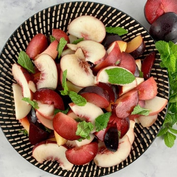 WHITE PEACH SALAD ON A BLACK PATTERNED PLATE WITH PLUMS AND MINT ON THE SIDE