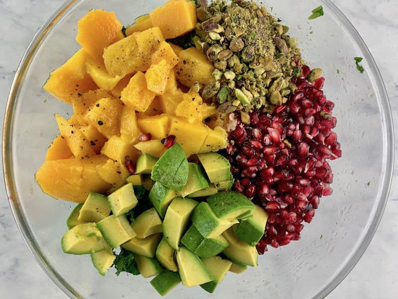 Kale mango salad ingredients in a glass bowl