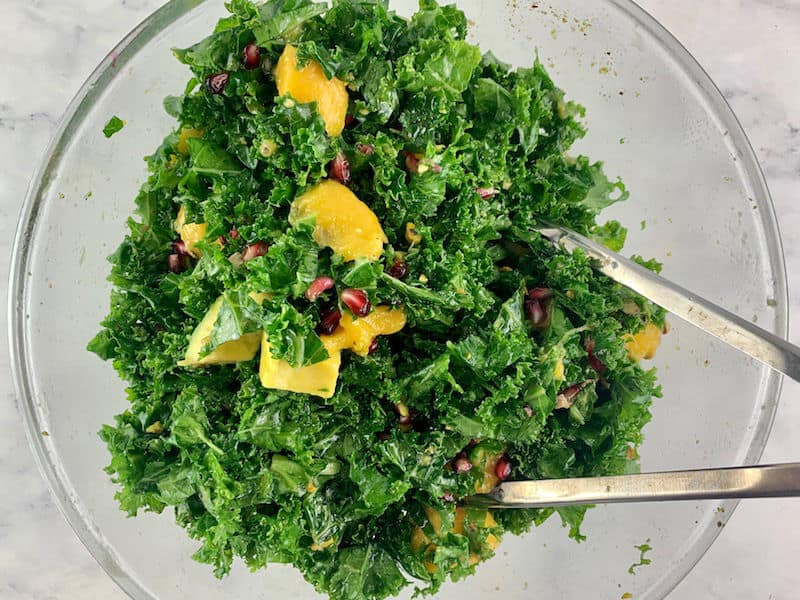 Mixinhpg kale mango salad in a glass bowl with tongs