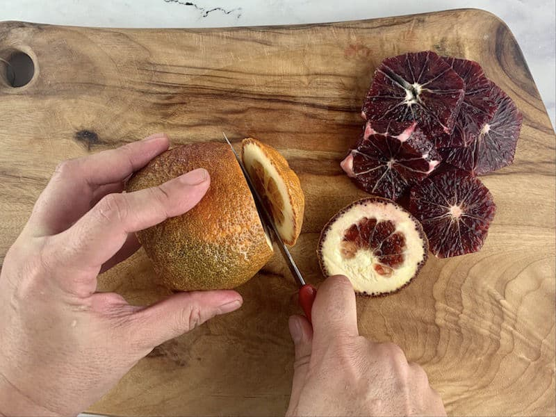 HANDS TRIMMING BLOOD ORANGE ON WOODEN BOARD WITH KNIFE