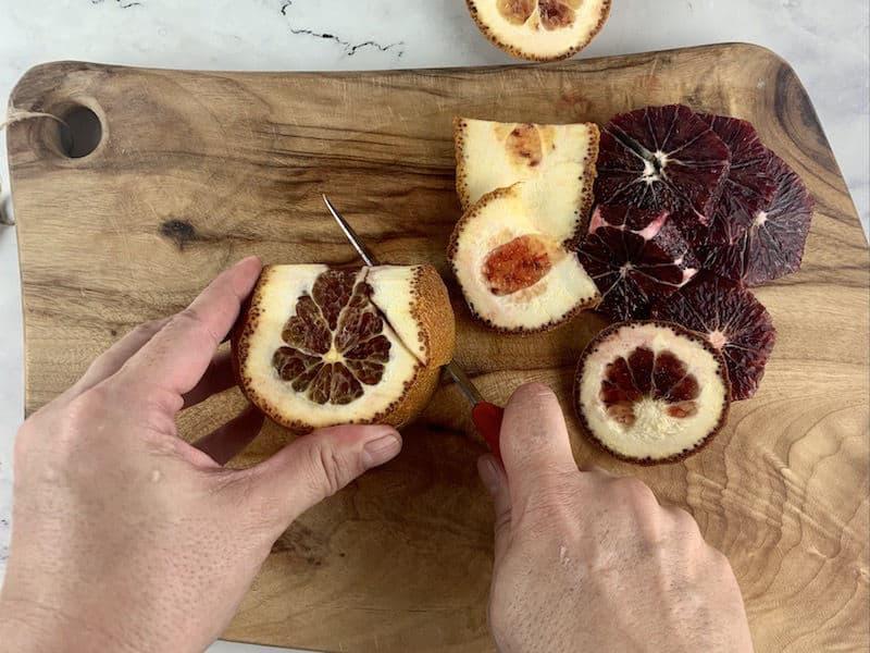 HANDS PEELING BLOOD ORANGE WITH KNIFE ON WOODEN BOARD