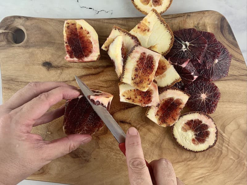 HANDS TRIMMING PITH FROM BLOOD ORANGE ON WOODEN BOARD