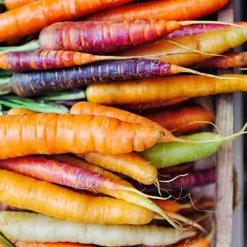 BUNCH OF COLOURFUL CARROTS IN A WOODEN CRATE