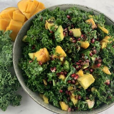 Kale mango salad in bowl with kale leaves and mango cheeks on the side